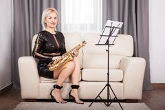 Saxophonist girl playing at her musical instrument in the living Royalty Free Stock Photo
