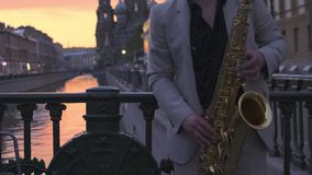 Saxophonist in a light suit on a bridge in the setting sun, plays the saxophone. Saxophonist in a light suit on a bridge in the setting sun, plays the saxophone stock video footage