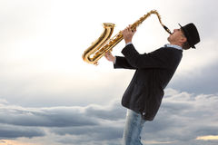 Saxophonist. Man playing on saxophone against the background of sky Stock Images