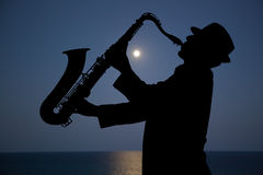 Saxophonist. Man playing on saxophone against the background of sunset Royalty Free Stock Photography