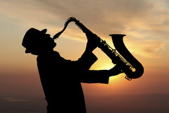 Saxophonist. Man playing on saxophone against the background of sunset Stock Photos
