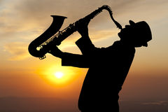 Saxophonist. Man playing on saxophone against the background of sunset Stock Photo