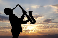 Saxophonist. Man playing on saxophone against the background of sunset Royalty Free Stock Image