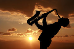 Saxophonist. Man playing on saxophone against the background of sunset Royalty Free Stock Photo
