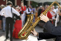 Saxophonist. Men playing on saxophone against the background of dance people Stock Photography