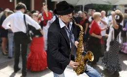 Saxophonist. Men playing on saxophone against the background of dance people Stock Photos