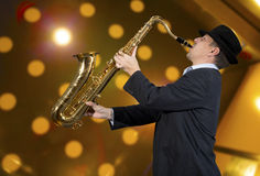 Saxophonist. Men playing on saxophone against the background of rock cafe Royalty Free Stock Images