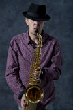 Saxophonist. Middle aged man playing on saxophone on grey background Royalty Free Stock Images