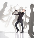 Saxophonist  playing against background with shadow of musicians Royalty Free Stock Photography