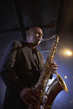 Saxophonist Playing Jazz. Low angle view of a musician playing saxophone in the jazz club Stock Images