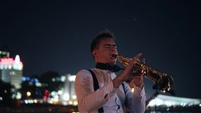 Saxophonist playing on the night promenade of the big city. The performance of a street musician in front of an audience stock footage