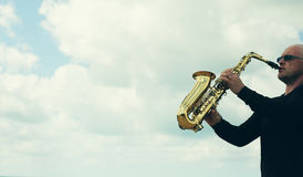 Saxophonist. Playing on saxophone outdoor. Old style photo Stock Photo