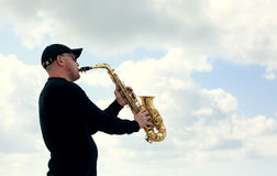 Saxophonist. Playing on saxophone outdoor. Old style photo Stock Photos