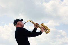 Saxophonist playing on saxophone outdoor Stock Image