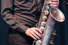 Saxophonist playing a tenor saxophone. Close up view of the hands of a male saxophonist playing a tenor saxophone in an orchestra, a reed woodwind instrument Royalty Free Stock Images