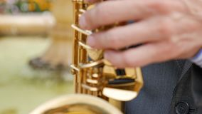 A saxophonist plays the saxophone. The musician plays the instrument on the background of wooden house frame with a working fountain. Finger work men stock video footage