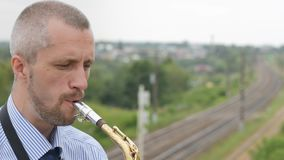 A saxophonist plays the saxophone stock video footage