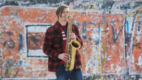Saxophonist plays the saxophone, in winter. Saxophonist plays the saxophone. white young man plays on a wind musical instrument outdoors. Legs of a musician stock video footage