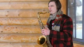 Saxophonist plays the saxophone, in winter. Saxophonist plays the saxophone. white young man plays on a wind musical instrument outdoors. Legs of a musician Royalty Free Stock Photos