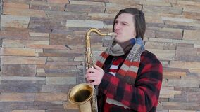 Saxophonist plays the saxophone, in winter. Saxophonist plays the saxophone. white young man plays on a wind musical instrument outdoors. Legs of a musician stock footage
