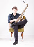 Saxophonist posing on chair Stock Image