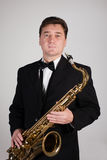 Saxophonist with a saxophone. On a gray background Royalty Free Stock Image