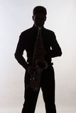 Saxophonist. Silhouette on grey background Stock Image