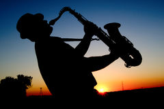 Saxophonist at sunset. Outline saxophonist on the background of the sun in the hot summer afternoons Royalty Free Stock Photos