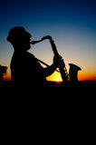 Saxophonist at sunset 2. Outline saxophonist on the background of the sun in hot summer evening Stock Photo