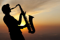 Saxophonist at sunset. Saxophonist. Woman playing on saxophone against the background of sunset Stock Photo