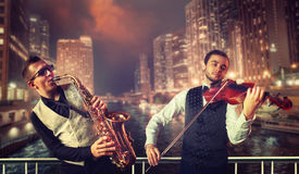 Saxophonist and violinst against night cityscape. Saxophonist and violinst playing melody against night cityscape background, musical duet. Jazz-man and fiddler Stock Photography