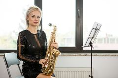 Saxophonist woman with her musical instrument at the window Stock Photo