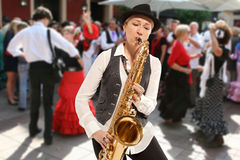 Saxophonist. Woman playing on saxophone against the background of dance people Stock Image