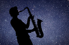 Saxophonist. Woman playing on saxophone against the background of starry sky Royalty Free Stock Photography