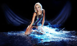 Saxy woman dancing in water on black , Stock Image