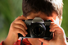 Say cheese!. Image of a boy taking picture with an SLR camera Stock Photos