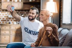 Happy men of different age taking a photo together. Say cheese. Positive young social worker looking excited while sitting on the sofa and taking a nice photo stock photography