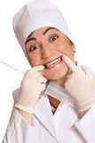 Say cheese to dentist. Humorous portrait of young grimacing woman in doctor' s uniform with huge syringe Royalty Free Stock Image
