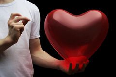 Say good bye to your love. Man's hand holding needle near heart Stock Photo