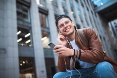 Say hello. Happy man meeting someone. Happy man listening to music with headphones from a smartphone on the street. stock photos