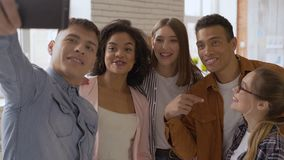 Say hello! mixed race group of 5 people. Cheerful people talking on a cell phone camera. teens laugh and say hi to the