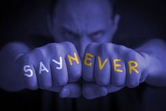 SAY NEVER written on an angry man's fists. SAY NEVER written on the fingers of an angry man's fists. Blue colored. Message concept image Stock Photo