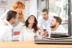 Say no to devices on weekend. Digital devices on a table with a friends in the background Royalty Free Stock Image