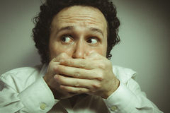 Say nothing, silence, man with intense expression, white shirt Stock Photos