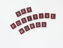 Say Positive Words with Curved Letters. Dark wooden tiles with words, Say Positive Words isolated on horizontal, white background royalty free stock photo