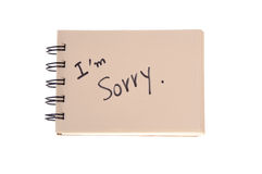 Say sorry. With a text message on paper Royalty Free Stock Image