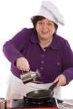 Say what??. Female chef pouring oil in the pan looking funny Stock Photography