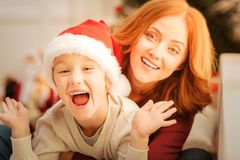 Extremely happy boy getting excited over christmas. Say what. Excited redhead kid sitting on a sofa with his mouth wide opened while relaxing with a family and Royalty Free Stock Photo