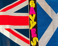 Say yes to Scottish independence. Text message ' say yes '  in colorful upper case letters placed between the Scottish Saltire and Union Jack flags concept of Stock Photography