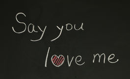 Say you love me. Written on blackboard with chalk Stock Photography